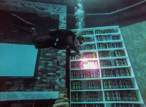 Moto, auto, una scacchiera, una finta libreria, una sala di giochi sono solo una piccola parte di quello che aspetta gli apneisti all'interno della piscina.  - Sputnik Italia