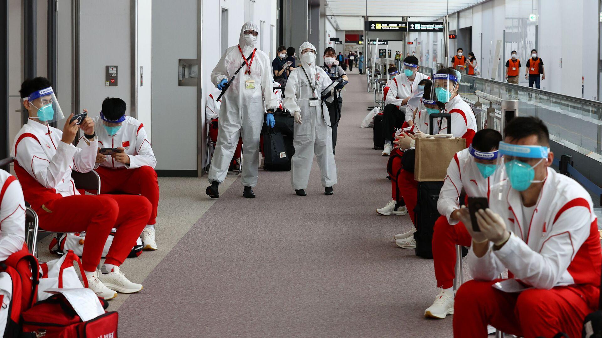 Сотрудники в защитных костюмах и сборная Китая в аэропорту Нарита  - Sputnik Italia, 1920, 28.07.2021