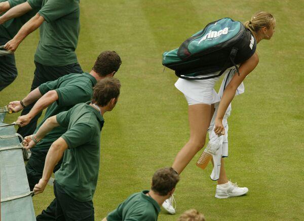 Il personale aspetta quando la tennista russa Maria Sharapova lasci il campo per coprirlo dalla pioggia che ha interrotto la partita a Wimbledon, 1 luglio 2004. - Sputnik Italia