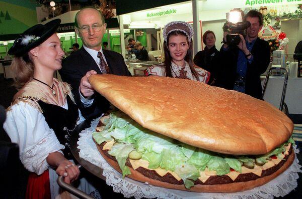 """L'ex ministro tedesco dell'agricoltura Jochen Borchert, circondato da donne vestite con costumi tradizionali tedeschi, controlla un hamburger gigante durante una prima visita della """"Gruene Woche"""" (Settimana verde), che è la più grande fiera mondiale per l'alimentazione e l'agricoltura , a Berlino 16 gennaio 1997. - Sputnik Italia"""