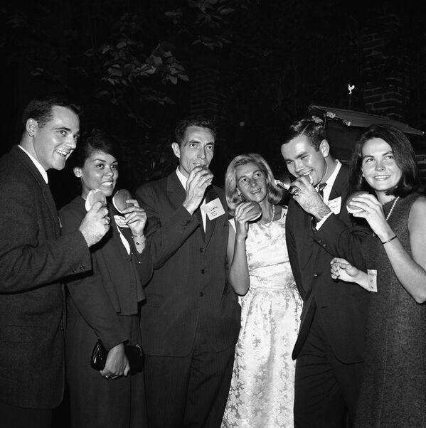 Il senatore Claiborne Pell e sua moglie Nuala mangiano hamburger con gli studenti del collegio durante una cena nel giardino della casa di Pell a Washington l'8 ottobre 1963.  - Sputnik Italia