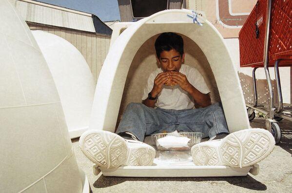 Daniel Espinoza, 11 anni, mangia un hamburger durante una pausa nella giornata di adozione di un cane, un programma che abbina i bambini a rischio del centro cittadino con animali che necessitano di amore e cura, in un negozio Petco, 26 aprile , 1997 a West Hollywood, in California.  - Sputnik Italia