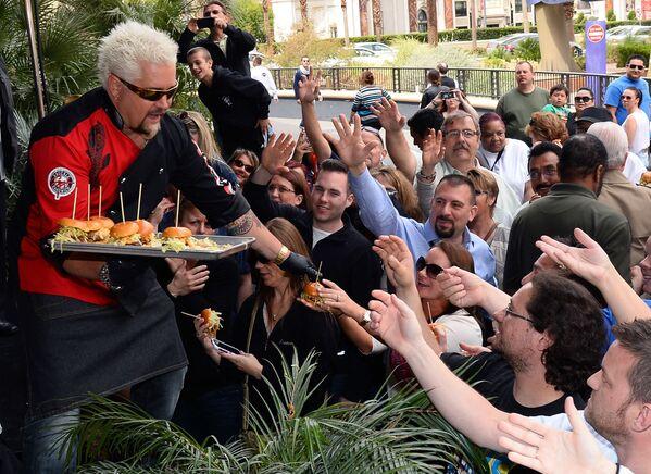 Lo chef e personaggio televisivo Guy Fieri offre hamburger agli ospiti durante un evento di benvenuto per Vegas Kitchen & Bar di Guy Fieri al Quad Resort & Casino il 4 aprile 2014 a Las Vegas, Nevada.  - Sputnik Italia