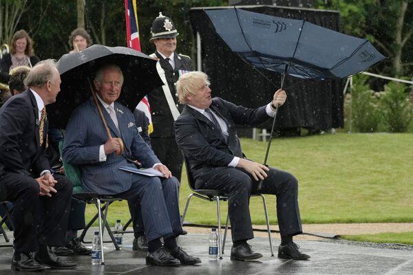 Il Principe Carlo e il primo ministro Boris Johnson si riparano dalla pioggia durante l'inaugurazione del memoriale della polizia del Regno Unito presso il National Memorial Arboretum ad Alrewas, in Inghilterra, 28 luglio 2021. - Sputnik Italia
