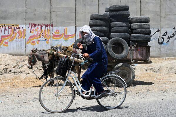 Un giovane va in bicicletta accanto a un carretto carico di pneumatici su una strada a Kabul, 27 luglio 2021. - Sputnik Italia