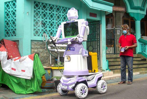 """Aseyanto, 53 anni, manovra il """"Delta Robot"""", realizzato con oggetti domestici come pentole, padelle e un vecchio monitor televisivo, a Surabaya,  Indonesia, il 7 agosto 2021. Il robot è in grado di svolgere una serie di compiti, come spruzzare disinfettante, consegnare cibo e soddisfare le esigenze dei residenti che si autoisolano a causa del Covid. - Sputnik Italia"""