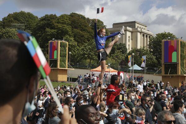 Una donna sventola la bandiera francese mentre esegue acrobazie nella fan zone delle Olimpiadi al Trocadero di Parigi, il 7 agosto 2021. - Sputnik Italia
