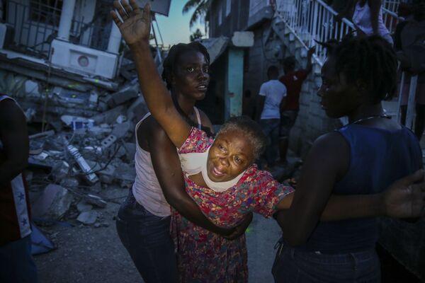 Una donna del nome Oxiliene Morency piange dal dolore dopo che il corpo della sua figlia di 7 anni Esther Daniel è stato ritrovato nelle macerie della loro casa distrutta dal terremoto a Les Cayes, Haiti, sabato 14 agosto 2021. - Sputnik Italia