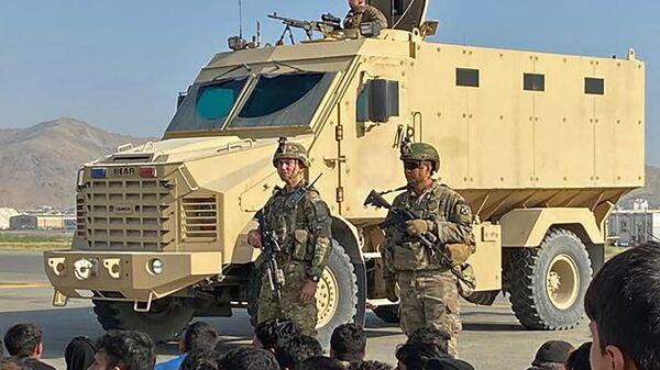 Афганские жители напротив американских солдатов в аэропорту Кабула  - Sputnik Italia