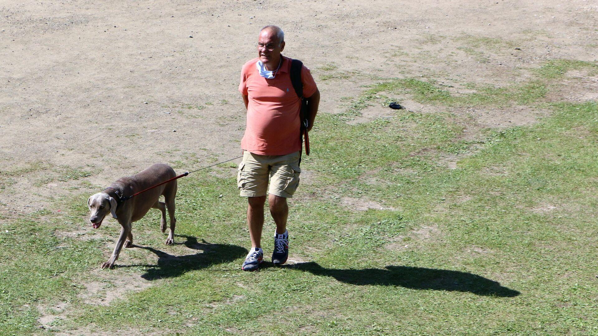 Un cane con un padrone fanno un giro in un parco in Italia - Sputnik Italia, 1920, 20.08.2021