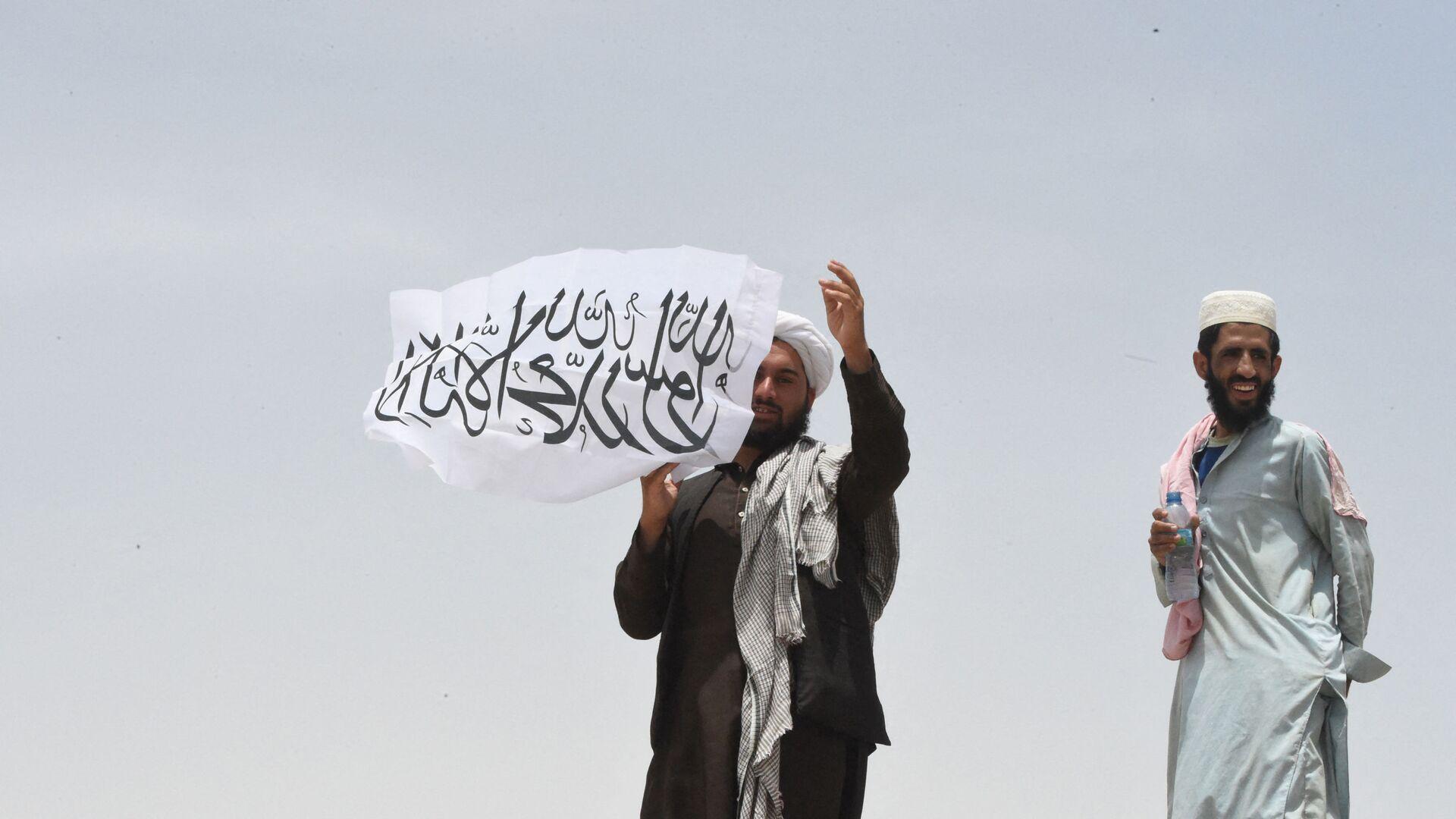 Uomo con la bandiera dei Talebani - Sputnik Italia, 1920, 26.08.2021
