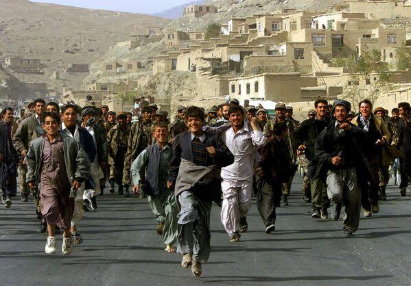 I residenti di Kabul scortano i combattenti dell'Alleanza del Nord che entrano nella capitale afghana Kabul, Afghanistan, il 13 novembre 2001. - Sputnik Italia