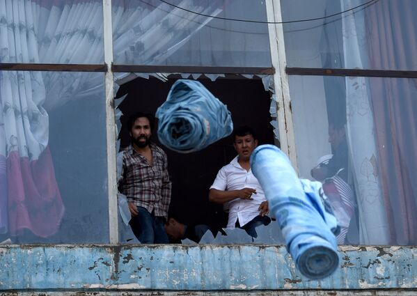 I negozianti afgani lanciano rotoli di tessuto fuori da una finestra mentre un incendio infuria nel centro commerciale Business di Kabul il 4 agosto 2016. Il 4 agosto è scoppiato un violento incendio in un centro commerciale nella parte occidentale di Kabul, causando gravi perdite ai negozianti. Ancora non si conoscono le cause dell'incendio. - Sputnik Italia