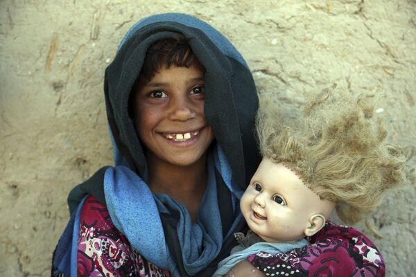 Una ragazza afgana in posa per una fotografia con la sua bambola alla periferia di Kabul, Afghanistan, martedì 29 maggio 2018. - Sputnik Italia