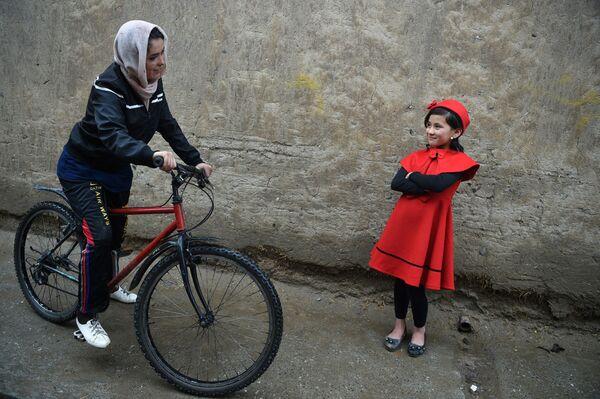 In questa foto scattata il 14 aprile 2019, la ciclista afghana Kobra Samim parla con una ragazzina sul ciglio della strada a Kabul.  - Sputnik Italia