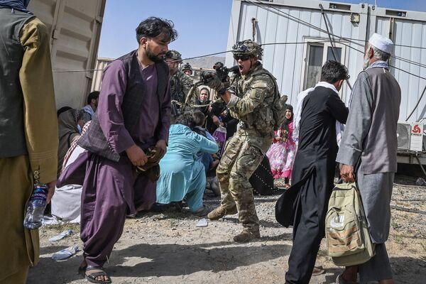 Un soldato americano punta il fucile verso un passeggero afghano all'aeroporto di Kabul il 16 agosto 2021, dopo che la capitale afghana è stata conquistata dai talebani (organizzazione terroristica vietata in Russia e molti altri Paesi). Migliaia di persone hanno preso d'assalto l'aeroporto della città cercando di fuggire dal Paese.  - Sputnik Italia
