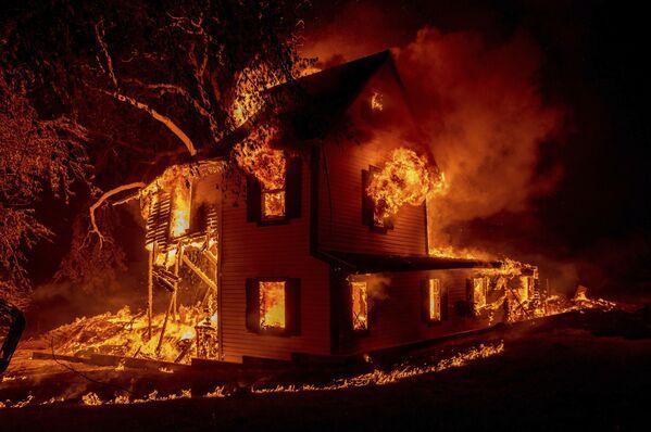 Una casa brucia su Jeters Road mentre il fuoco dell'incendio Dixie assedia l'autostrada 395 a sud di Janesville, in California, USA, lunedì 16 agosto 2021.  - Sputnik Italia