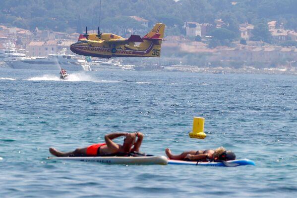 Bagnanti mentre un aereo Canadair vola sopra di loro dopo essere stato riempito d'acqua per aiutare a spegnere un grave incendio scoppiato nella regione del Var, nel Golfo di Saint Tropez, in Francia, il 17 agosto 2021. - Sputnik Italia