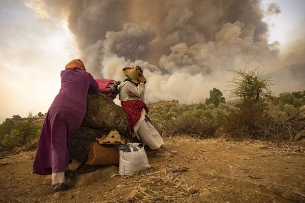 Le donne marocchine si trovano su una strada in montagna con le loro cose mentre gli incendi boschivi assediano una foresta nella regione di Chefchaouen, nel nord del Marocco, il 15 agosto 2021 - Sputnik Italia