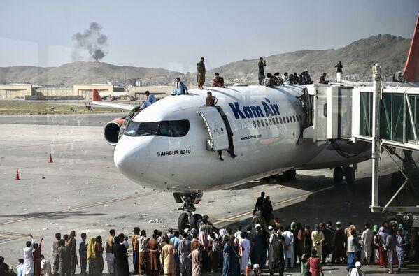 Gli afghani cercano di arrampicarsi su un aereo all'aeroporto di Kabul nel tentativo di fuggire dal Paese conquistato da pare dei talebani (organizzazione terroristica vietata in Russia e molti altri Paesi), il 16 agosto 2021.  - Sputnik Italia