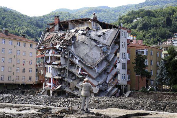 Un uomo guarda un edificio distrutto, nella città di Bozkurt, nella provincia di Kastamonu, in Turchia, sabato 14 agosto 2021. Il bilancio delle vittime di gravi inondazioni e frane nella costa turca è salito ad almeno 44, ha detto sabato l'agenzia di emergenza e disastri del Paese . - Sputnik Italia