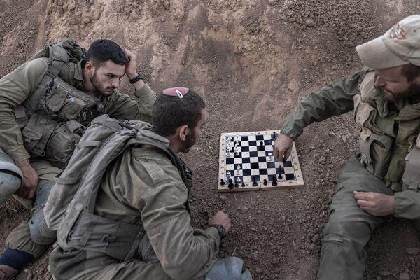 I soldati israeliani giocano a scacchi nella loro posizione vicino al confine Israele-Gaza, lunedì 16 agosto 2021. Le sirene dei raid aerei hanno suonato lunedì nel sud di Israele dopo che un razzo è stato lanciato dalla Striscia di Gaza, il primo dopo la guerra di 11 giorni tra israeliani e palestinesi a maggio. - Sputnik Italia