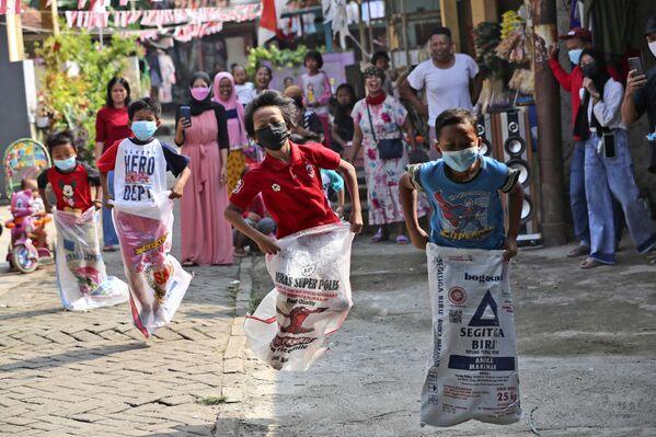 I bambini in mascherina protettiva prendono parte a una gara di corsa con i sacchi durante le celebrazioni del Giorno dell'Indipendenza a Jakarta, Indonesia, martedì 17 agosto 2021. - Sputnik Italia