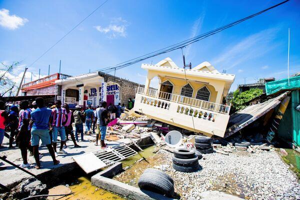 Persone si radunano accanto a una casa distrutta in seguito al terremoto di magnitudo 7.2 a Les Cayes, Haiti, 14 agosto 2021. - Sputnik Italia