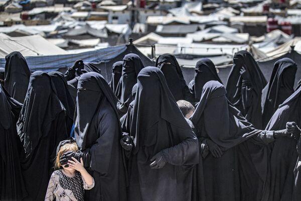 Donne  fanno la fila per ricevere pacchi di aiuti umanitari nel campo di al-Hol, gestito dai curdi, che ospita i parenti di sospetti combattenti del gruppo dello Stato Islamico (ISIS, organizzazione terroristica vietata in Russia e molti altri Paesi), il 18 agosto 2021. - Sputnik Italia