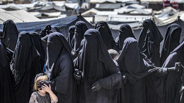 Женщины с детьми выстраиваются в очередь, чтобы получить посылки с гуманитарной помощью в управляемом курдами лагере Аль-Хол, где содержатся родственники предполагаемых боевиков группировки Исламское государство*, в сирийской провинции Хасакех - Sputnik Italia