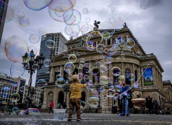 Un ragazzo gioca con le bolle di sapone di fronte alla Vecchia Opera di Francoforte, Germania, martedì 17 agosto 2021. - Sputnik Italia