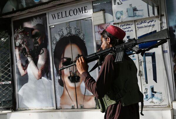 Un combattente talebano passa davanti a un salone di bellezza con immagini di donne daneggiate con vernice spray a  Kabul il 18 agosto 2021. - Sputnik Italia