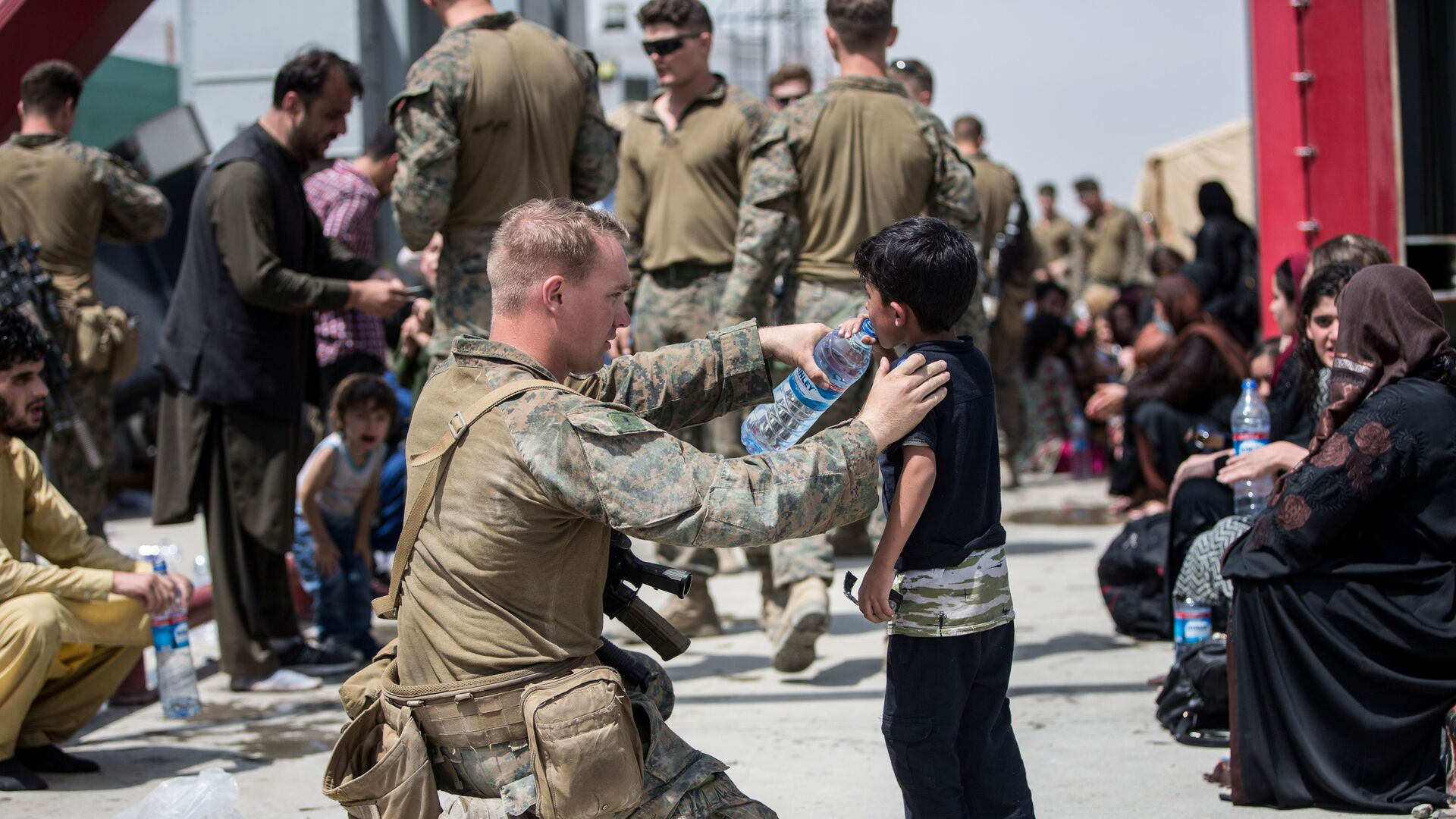 Американский солдат дает воду ребенку в аэропорту Кабула  - Sputnik Italia, 1920, 05.09.2021