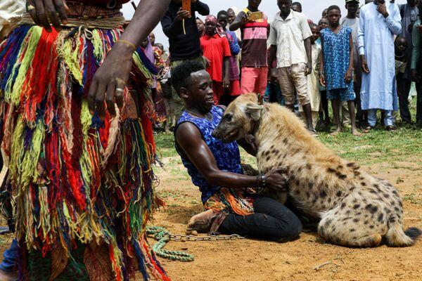 Abdullahi Jahun, 24 anni, gioca con una iena. Jahun ha imparato a domare e addestrare la iena da suo padre e ora si guadagna da vivere facendo tour nel nord della Nigeria, intrattenendo la folla con il suo animale. - Sputnik Italia