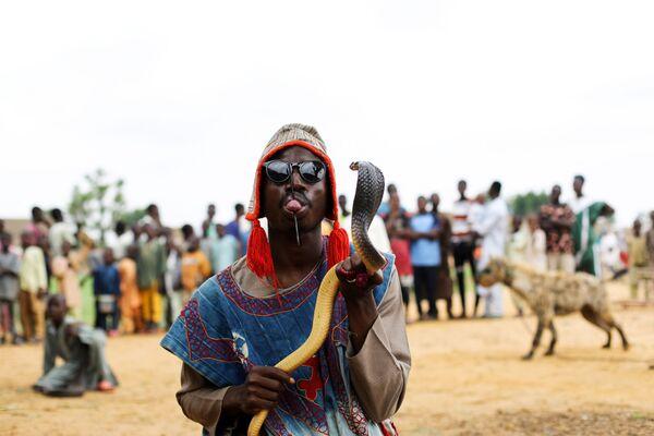 Abubakar Usaini mostra il suo piercing sulla lingua mentre tiene in mano un pitone durante un circo a Gabasawa. - Sputnik Italia