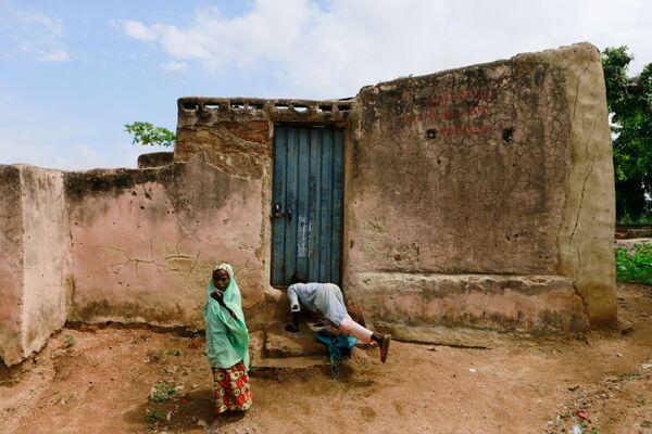 Un ragazzo sale a casa di Yaya Kawu a Rano, in Nigeria. Kawu, che vive con una iena e diversi serpenti, sostiene che i suoi animali sono considerati parte della vita della sua comunità. - Sputnik Italia