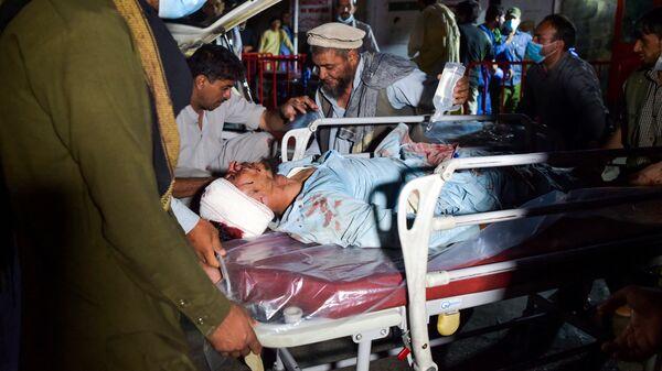 Медицинский персонал переносят раненого на носилках для оказания помощи после двух взрывов у аэропорта Кабула, в результате которых не менее пяти человек погибли и десятки получили ранения, Афганистан - Sputnik Italia