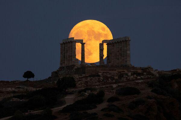 Una luna piena illumina il tempio di Poseidone a Sounio, in Grecia. - Sputnik Italia
