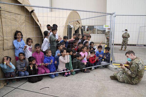 Un soldato americano suona la chitarra per i bambini afghani evacuati di recente alla base di Ramstein degli Stati Uniti, Germania. - Sputnik Italia