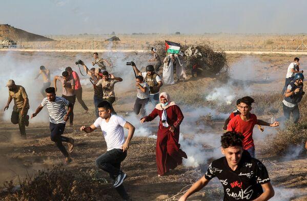 Dimostranti e giornalisti palestinesi scappano dai gas lacrimogeni sparati dalle forze di sicurezza israeliane durante una protesta lungo la recinzione di confine, a est di Khan Yunis, nel sud della Striscia di Gaza. - Sputnik Italia