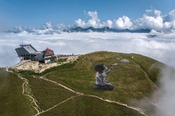 """Un gigantesco land-art dell'artista francese Guillaume Legros intitolato: """"Un nuovo respiro"""", che rappresenta un ragazzo che soffia nuvole. - Sputnik Italia"""