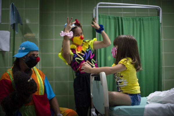 Una ragazza è intrattenuta dai clown mentre aspetta nella sala di controllo dopo essere stata vaccinata a L'Avana, Cuba. - Sputnik Italia