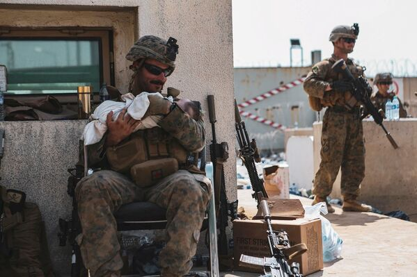 Un marine statunitense assegnato tiene in braccio un bambino durante l'evacuazione all'aeroporto internazionale Hamid Karzai, Kabul, Afghanistan. - Sputnik Italia