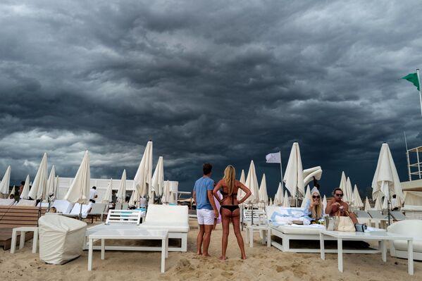Le persone guardano le nuvole scure mentre si trovano su una spiaggia a Ramatuelle, vicino a Saint-Tropez, nel sud della Francia, 24 agosto 2021. - Sputnik Italia