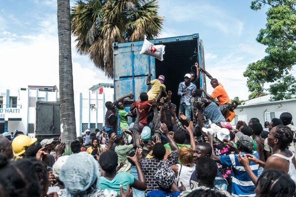 Un uomo lancia un sacco di riso in una folla di vittime del terremoto a Les Cayes, Haiti. - Sputnik Italia