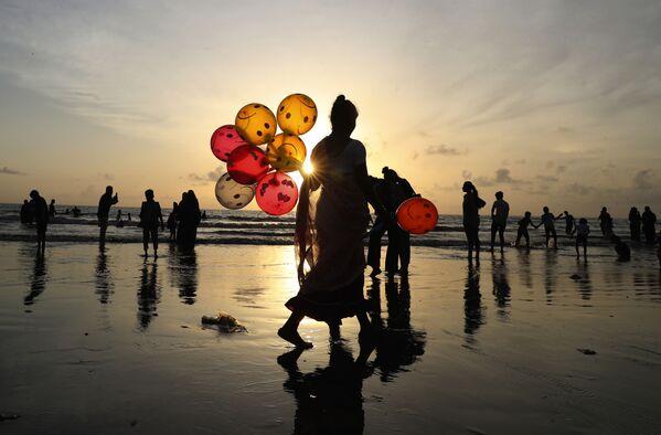 Una donna vende palloncini in una spiaggia di Juhu a Mumbai, India. - Sputnik Italia