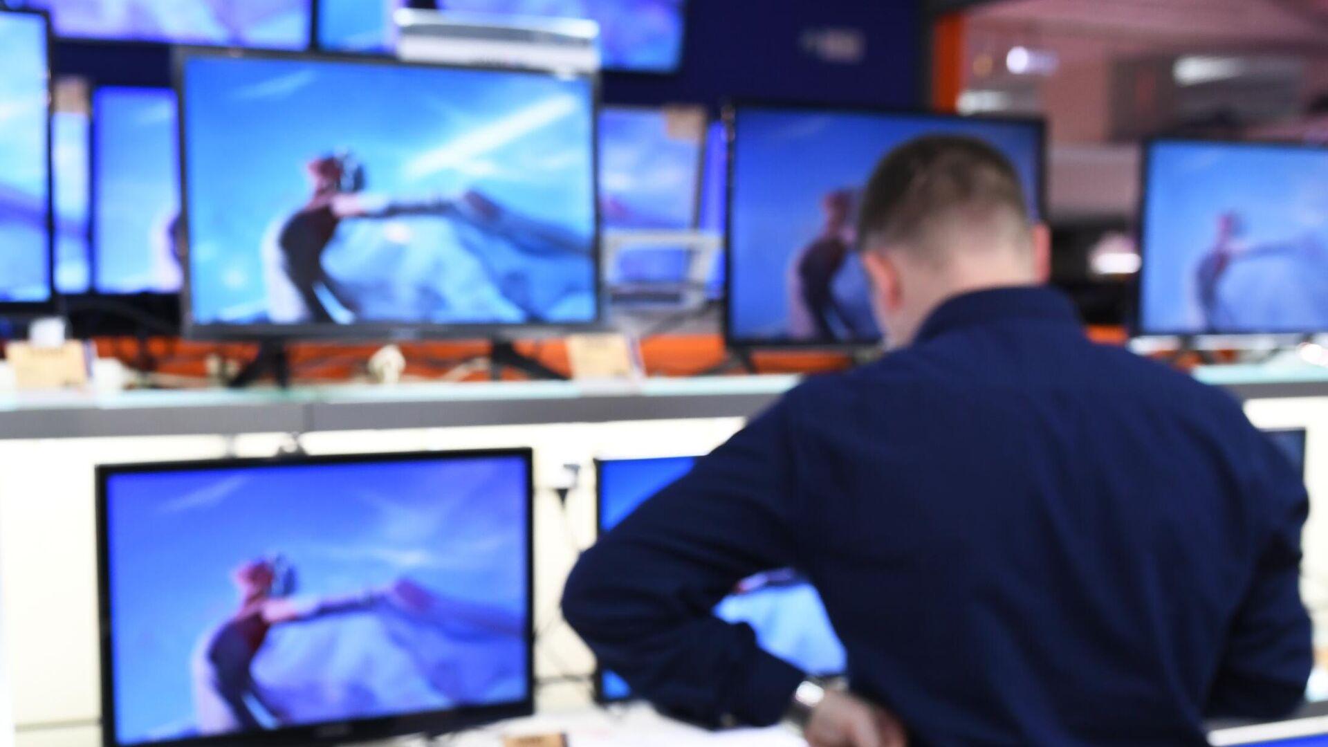 Un uomo sceglie il televisore da acquistare - Sputnik Italia, 1920, 30.08.2021