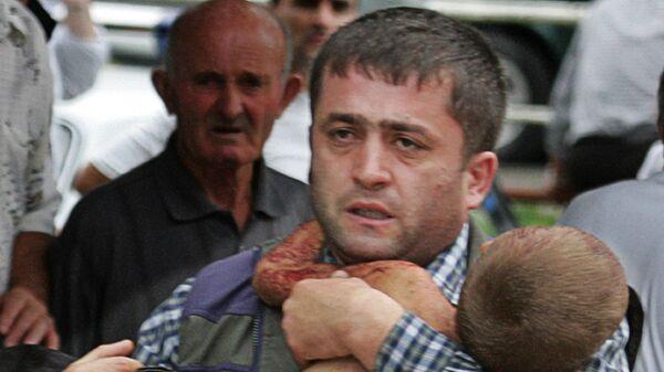 Мужчина с раненым спасенным ребенком в Беслане  - Sputnik Italia