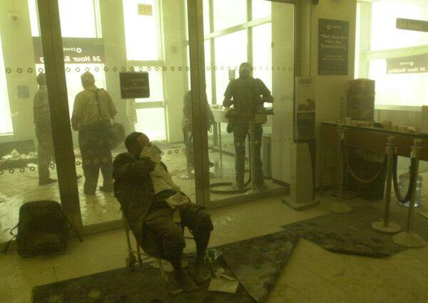 Un uomo ferito aspetta i soccorsi, mentre altri si rifugiano in una banca vicino alle torri del World Trade Center l'11 settembre 2001 a New York. - Sputnik Italia