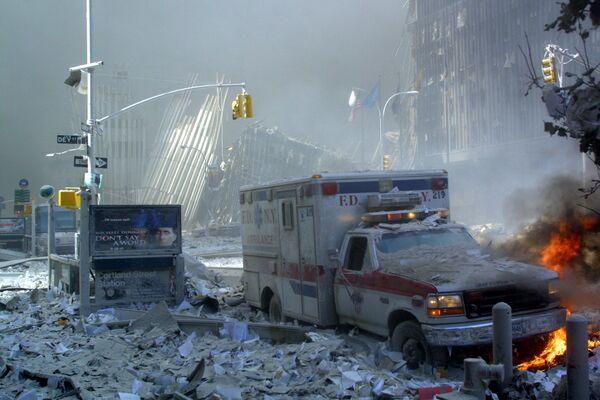 Un'ambulanza ricoperta di detriti è in fiamme dopo il crollo della prima torre del World Trade Center l'11 settembre 2001 a New York. - Sputnik Italia